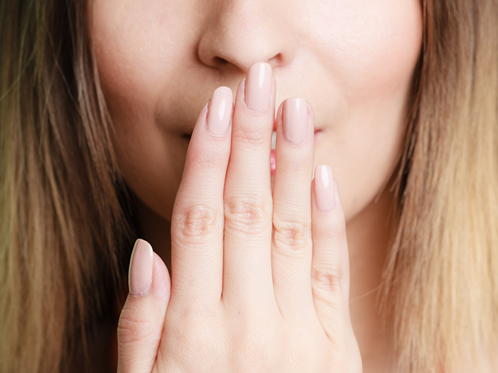Part of face woman covering her mouth with hand